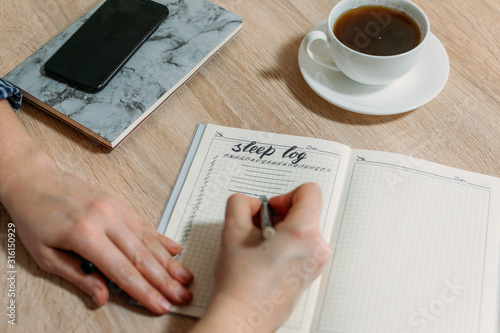 Fotografia, Obraz Woman hand with Sleep Log or Diary on table