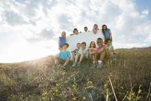 Portrait Of Schoolchildren With Blank Billboard On Field