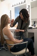 Female Makeup Artist Applying Makeup To Model, Preparing For Photo Shoot
