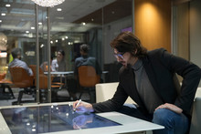 Businessman Using Interactive Touch Table In Office