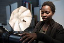 Focused Female Photographer Preparing Lighting Equipment For Photo Shoot In Studio