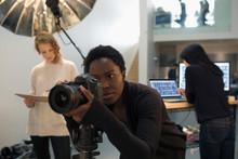 Focused Female Photographer Using Digital Camera At Photo Shoot In Studio