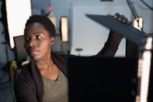 Female Photographer Adjusting Lighting Equipment For Photo Shoot In Studio