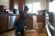 Young woman moving into new house, unpacking cardboard boxes in kitchen