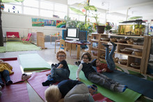 Tired Preschool Students Resting On Yoga Mats During Nap Time