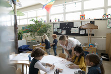 Preschool Teacher And Students Using Stencils On Poster In Classroom