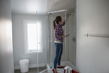 Woman Replacing Shower Head With Eco-friendly Low-flow Shower Head, DIY