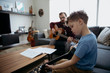 Father teaching son how to play guitar in living room