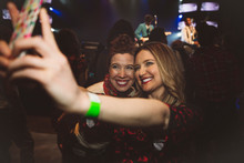 Smiling, Confident Millennial Women Friends Taking Selfie With Camera Phone At Music Concert