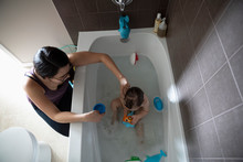 Mother Bathing Baby Son Taking...
