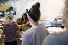 Female Worker Helping Customer...