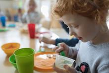 Preschool Girl Eating, Finishing Apple Sauce During Snack Time