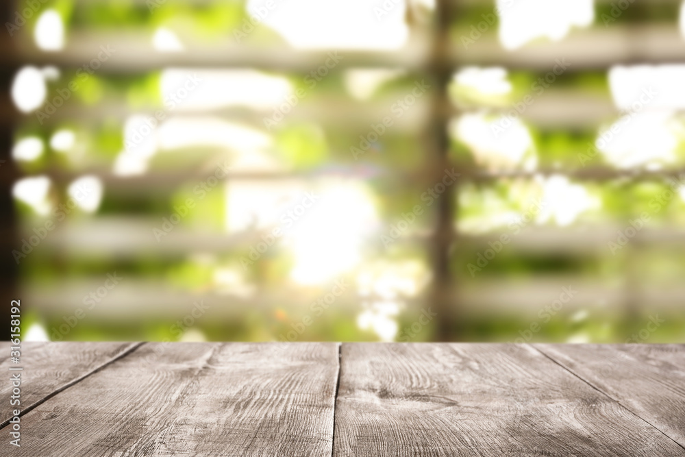 Fototapeta Empty wooden table in front of window. Sunny morning