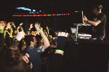 Crowd Dancing, Cheering DJ On Nightclub Stage