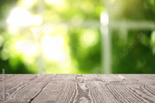 Empty wooden table in front of window. Sunny morning