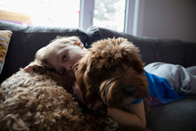 Portrait Affectionate Boy Cuddling Cute Dog On Living Room Sofa