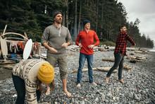 Friends Enjoying Weekend Surfing Getaway, Throwing Rocks On Rugged Beach