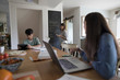 Mother writing grocery list on blackboard in kitchen while tween daughter and son do homework