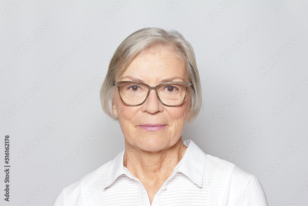 Fototapeta Portrait picture of a senior woman wearing glasses on neutral gray background.