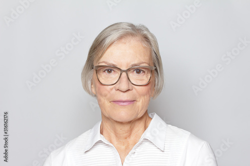 Obraz Portrait picture of a senior woman wearing glasses on neutral gray background. - fototapety do salonu