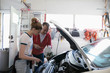 Father teaching tween daughter how to change oil in car