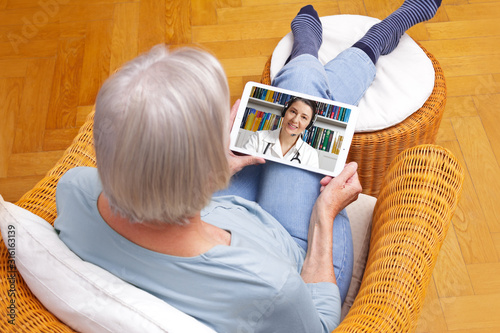 telemedicine concept, old woman with tablet pc during an online consultation with her doctor in her living room Fototapeta