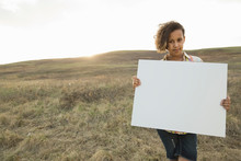 Portrait Of Schoolgirl Holding Blank Signboard On Field