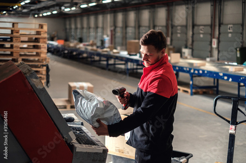 Leinwand Poster Courier picks up package on a warehouse