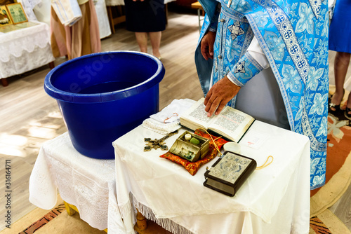 The sacrament of the rite baptism of a child in an Orthodox Christian church Canvas Print