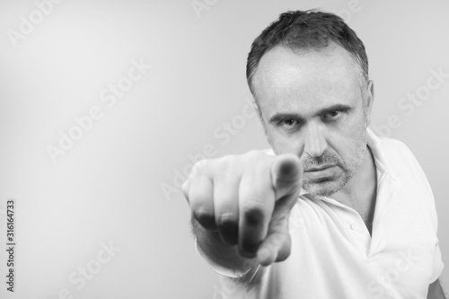 uomo di mezza età con polo bianca su sfondo neutro punto il dito contro Canvas Print