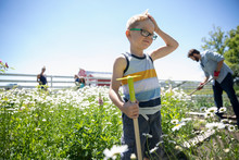 Boy Gardening With Family In S...