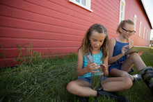 Sisters With Insect Jar And Digital Tablet Sitting In Grass Along Red Barn On Rural Farm