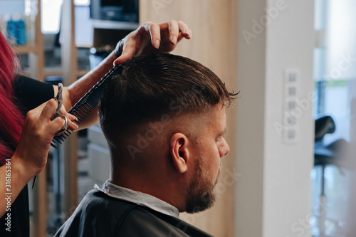 Man getting a haircut by hairdresser at the salon
