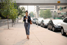 Businesswoman Walking And Usin...