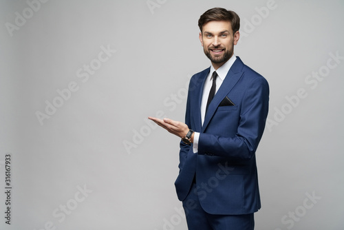 Obraz Portrait of a young businessman pointing on a copyspace with his finger - fototapety do salonu