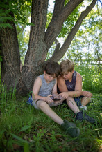 Brothers Using Smart Phone Und...