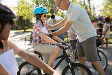 Father Pinning Marathon Bib On Sun Preparing For Bike Race At Summer Neighborhood Block Party