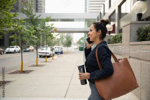 Businesswoman with coffee talking on smart phone on city sidewalk - 316169182