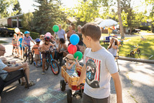 Boy Pulling Wagon, Leading Parade At Summer Neighborhood Block Party In Park