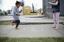 Girl Playing Hopscotch On Sidewalk