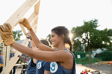 Volunteers Lifting Frame, Helping Build House