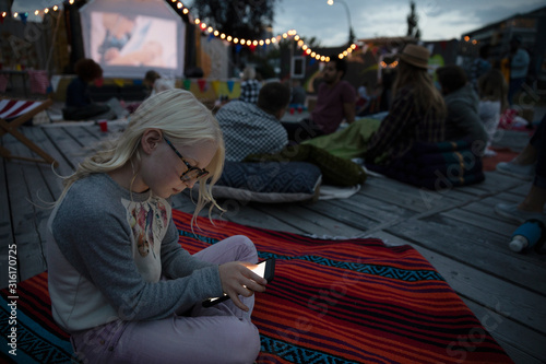 Girl using smart phone at movie in the park