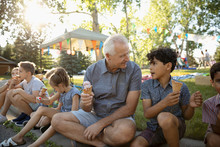 Grandfather And Grandson Eating Ice Cream Cones On Curb At Summer Neighborhood Block Party In Park