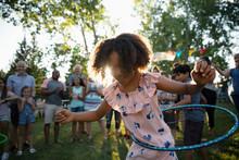 Playful Girl Spinning In Plastic Hoop At Summer Neighborhood Block Party In Park