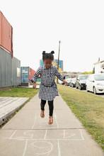 Cute Girl Playing Hopscotch On Sidewalk