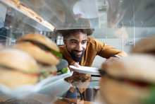 Smiling Cafe Worker Reaching In Display Case For Sandwich