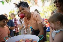 Playful Boy Splashing, Bobbing For Apples At Summer Neighborhood Block Party In Park