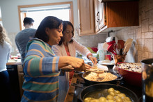 Latinx Senior Women Cooking In...