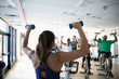 Female instructor with dumbbells leading spin class in gym