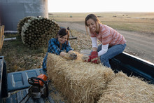 Female Farmers Moving Hay Bale...